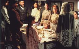 A scene from the movie Fiddler on the Roof, of a Jewish family celebrating the Sabbath meal. A woman wears a prayer shawl and lights candles, and her smiling family stands around the table.