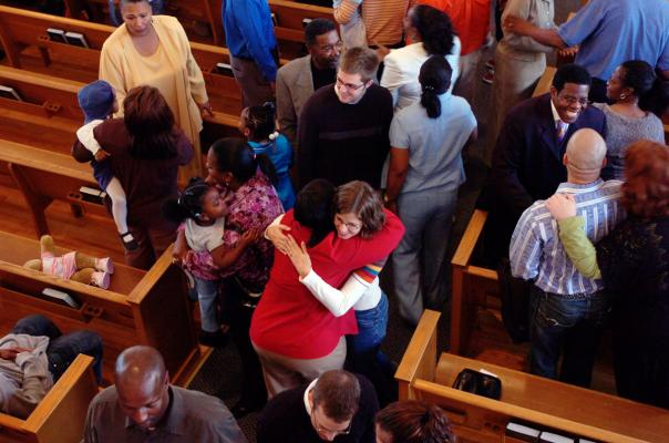 A top-down view of smiling people leaving their church pews to shake each other's hands or hug each other